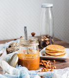 Peanut butter to eat a teaspoon of jars, pancakes Royalty Free Stock Images