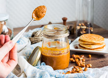 Peanut butter to eat a teaspoon of jars, pancakes Stock Photography