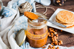 Peanut butter to eat a teaspoon of jars, pancakes Royalty Free Stock Photos