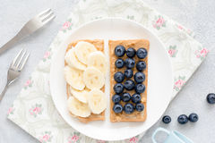 Peanut butter toast with banana and blueberries. Healthy vegan peanut butter toasts with blueberries and banana slices on white plate. Top view Stock Photo