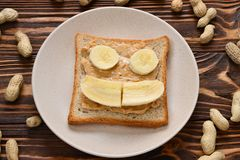 Peanut butter toast with banana slices on wooden background stock image