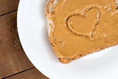 Peanut butter toast with heart shape on white against wood Royalty Free Stock Photography