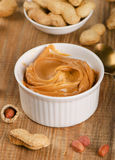 Peanut butter in  white bowl with peanuts. Stock Photos