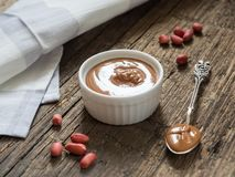 Peanut butter in a white bowl on a wooden table. Natural healthy nutrition and organic food stock image