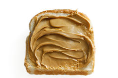 Peanut butter on white bread. Slice of white bread with swirled creamy peanut butter against white Stock Image
