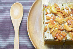 Peanut and cashew nut cake. On wooden plate Royalty Free Stock Photo