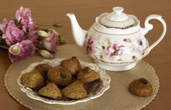 Peanut cookies, Teapot and flowers on the table Royalty Free Stock Image