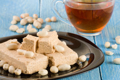 Peanut halva in the plate on a blue wooden background Stock Photos