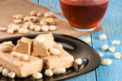 Peanut halva in the plate on a blue wooden background Royalty Free Stock Images