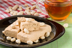 Peanut halva in the plate on a green wooden background Royalty Free Stock Photography