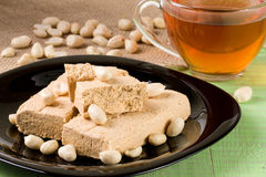 Peanut halva in the plate on a green wooden background Royalty Free Stock Photos