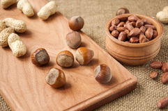 Peanut,  hazelnuts in wooden bowls on wooden and burlap, sack background Stock Images