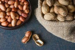 Peanut in nutshell in burlap sack or sackcloth on wooden background. Composition of peanuts. Peanut in nutshell in burlap sack or sackcloth and brown bowl on royalty free stock images