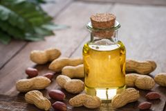Peanut oil in glass bottle and peanuts on wooden table Stock Image