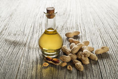 Peanut oil. In a glass bottle on a wooden background royalty free stock photos