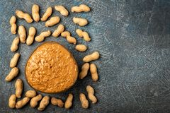 .peanut paste in an open jar and peanuts in the peel scattered on the table royalty free stock image