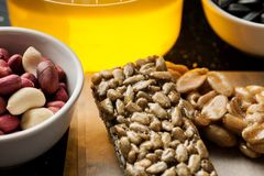 Peanut and sunflower seeds brittle with honey jar and raw ingredients in the white ceramic bowls stock photo
