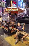 Times Square, New York City, New York, United States - circa 2012 -peanut vendor sitting in chair at night. Peanut vendor wearing I love new york tee shirt royalty free stock image