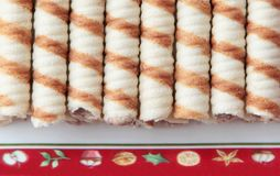 Peanut waffle rolls on christmas plate. Crispy peanut and coconut waffle rolls on christmas mat Royalty Free Stock Image