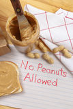 Peanut Warning. Overhead view of peanut butter on bread with red crayon warning against peanuts which are a dangerous allergen for many children and adults Royalty Free Stock Image