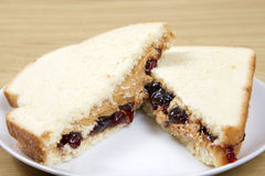 Peanutbutter and Jelly Sandwich cut in half served on plate. Traditional Peanut butter and Jelly Sandwich on white bread. cut in half stacked criss cross on a stock photography