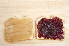 Peanutbutter and Jelly Sandwich on white bread open face. Traditional Peanut butter and Jelly Sandwich on white bread. open face on a light wood table stock photos