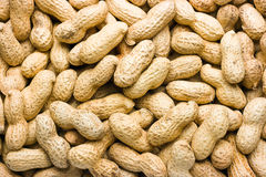 Peanuts. In their shell textured food background Stock Images