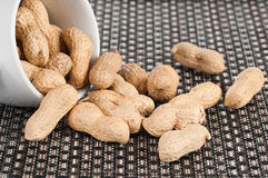 Peanuts. Falling out of a white bowl Royalty Free Stock Image