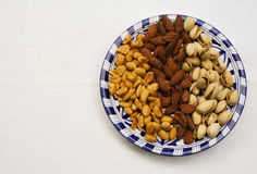 Peanuts, almond, pistachio nuts on a blue and white plate. On a white textured background Royalty Free Stock Images