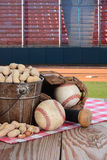 Peanuts and Baseball Stadium. A bucket of peanuts and baseball equipment on a wood picnic table with a field and stadium in the background Royalty Free Stock Photo