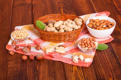 Peanuts in basket, different nuts cleaned, towel on dark wood. Stock Images