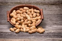 Peanuts in basket on old wood background. Stock Photography