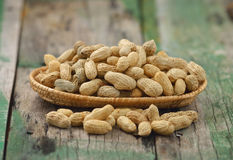 Peanuts in the  basket on wood Stock Photo