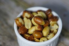 Peanuts or beer nuts in a white bowl on the table Stock Photo