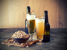 Peanuts and a Beer. On wooden table Royalty Free Stock Photo