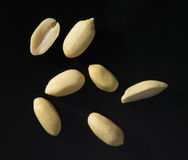 Peanuts on black background lit by harsh light Royalty Free Stock Photo
