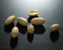 Peanuts on black background lit by harsh light Royalty Free Stock Photos