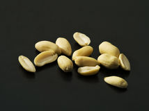 Peanuts on black background lit by harsh light Royalty Free Stock Images