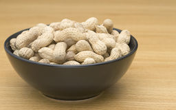 Peanuts in a black bowl Stock Photography