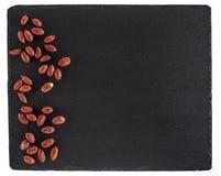 Peanuts on black slate board. Isolated on white background. Stock Image