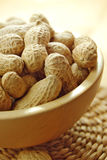 Peanuts in a bowl. Peanuts in a wooden bowl and a straw stand Royalty Free Stock Photo