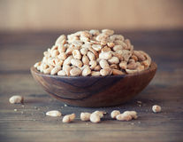 Peanuts. Bowl of salted  peanuts on wooden table Royalty Free Stock Photography