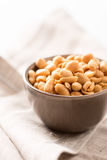 Peanuts in a bowl on tablecloth close up Stock Photography