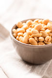 Peanuts in a bowl on tablecloth Stock Images