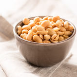Peanuts in a bowl on tablecloth square Royalty Free Stock Photos