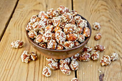 Peanuts in caramel with sesame on wooden board Royalty Free Stock Image