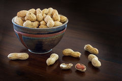 Peanuts in a ceramic bowl on a dark brown table, copyspace Royalty Free Stock Image