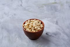 Peanuts in ceramic bowl isolated over white textured backround, top view, close-up. Shelled peanuts in ceramic bowl isolated over white textured background, top stock photography