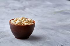 Peanuts in ceramic bowl isolated over white textured backround, top view, close-up. Shelled peanuts in ceramic bowl isolated over white textured background, top Stock Photos