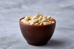 Peanuts in ceramic bowl over white textured backround, top view, close-up. Shelled peanuts in ceramic bowl over white textured background, top view, close-up stock image